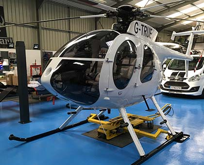 chopper spotter sitting below a helicopter in a hangar
