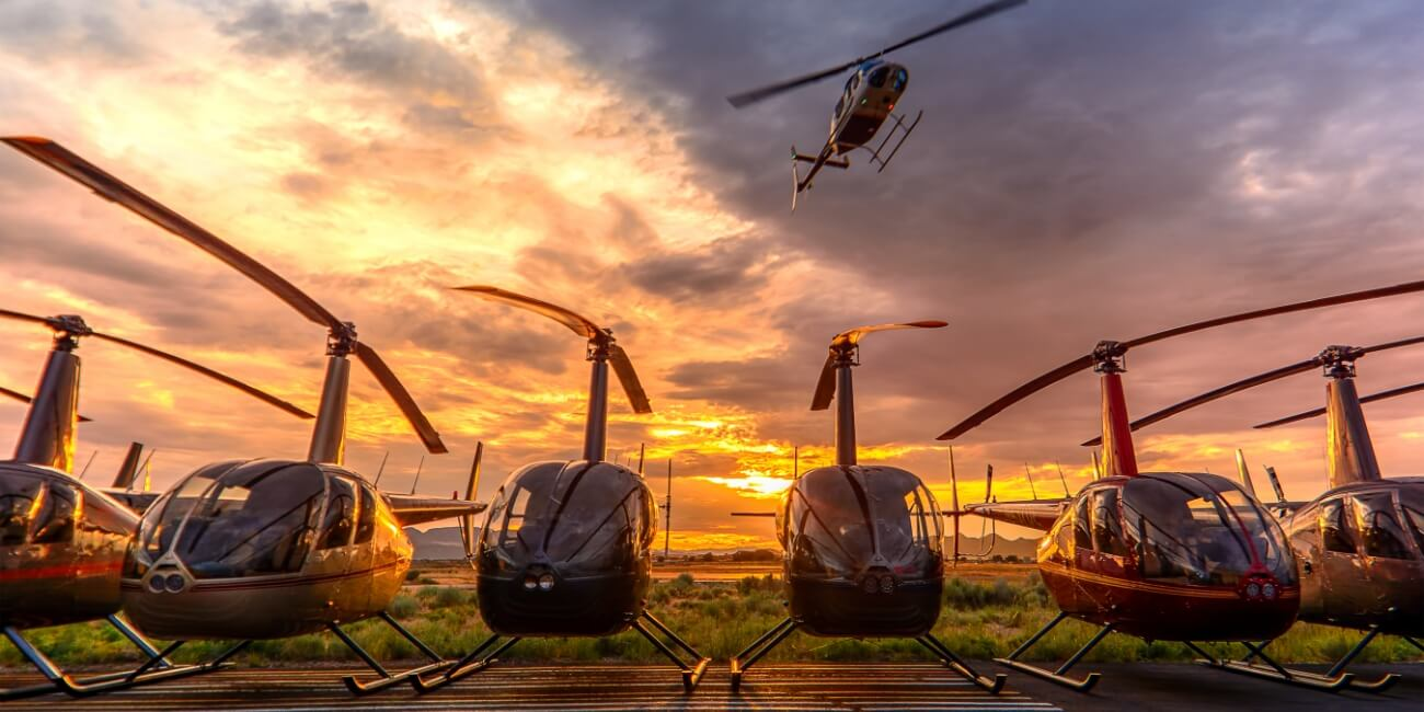 row of helicopters in an airfield
